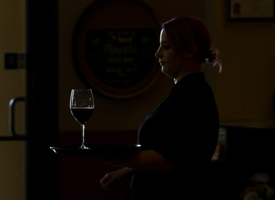 A waitress is silhouetted as she serves a glass of wine at Osorio's Latin Fusion in Grand Chute.