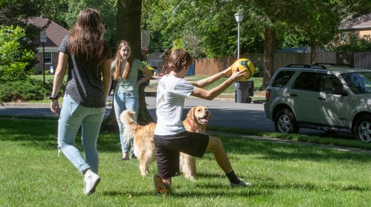 The Keoghs playing soccer with the family dog in the front yard of their Toms River home.