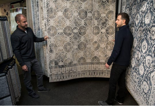 Carpet Yard, a 32-year old, family-owned provider of carpet, area rugs, wood flooring, and other floor coverings that's based in Freehold. CJ Winowski and his brother Jason look over an area rug. 