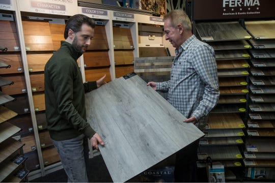 Carpet Yard, a 32-year old, family-owned provider of carpet, area rugs, wood flooring, and other floor coverings that's based in Freehold. Justin Winowski and Tom Higgins look over LVT flooring available at the store. 