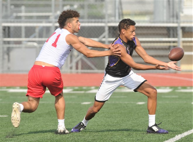 A Merkel player, right, makes a catch in front of an Electra defender during the Albany 7-on-7 Division III state qualifying tournament Friday at McMurry's Wilford Moore Stadium. Electra won, 26-24.