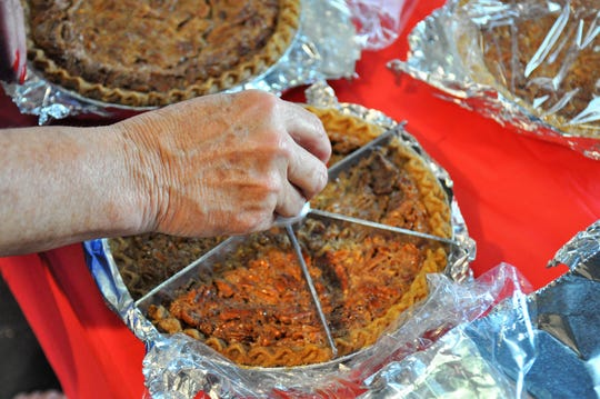 Janelle Campbell tests a slicer on a donated pie on Friday that will be served during the Cisco Pie Fest pie buffet on Saturday.