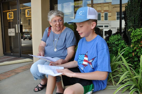 Kathie Cherry and her grandson Carson Cherry, 11, look over the Cisco Pie Fest pie baking rules while shopping in Cisco on Friday.