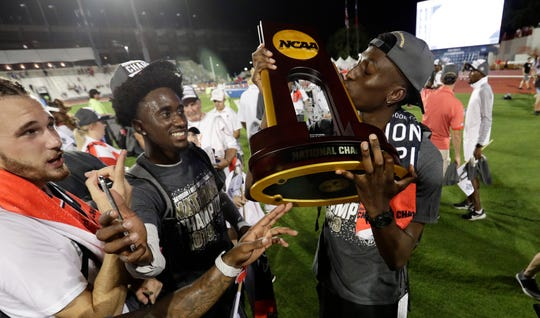 Texas Tech's Justin Hall kisses the trophy as he celebrates with teammates after the Red Raiders won the men's title at the NCAA outdoor track and field championships June 7 in Austin.
