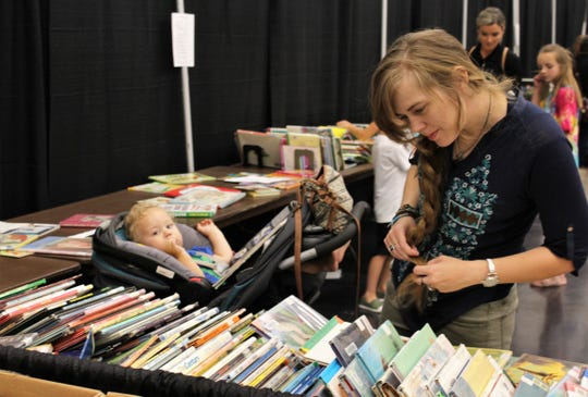 Kiera Boerckel looks through children's books with Malakai, who's nearly 20 months, pauses from his reading to look around Friday at the Friends of the Abilene Public Library sale at the Abilene Convention Center.