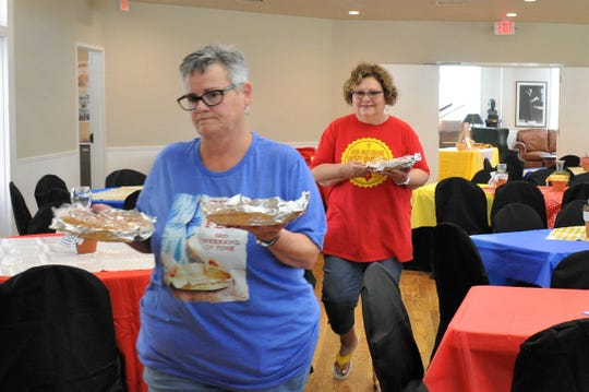 Debbie Rice, left, and Janelle Campbell carry donated pies on Friday that will be served during the Cisco Pie Fest pie buffet at the Conrad Hilton Center Saturday.