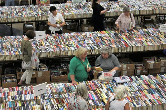 Book browsers search for interesting titles and sometimes discuss their finds Friday at the Friends of the Abilene Public Library sale at the Abilene Convention Center.
