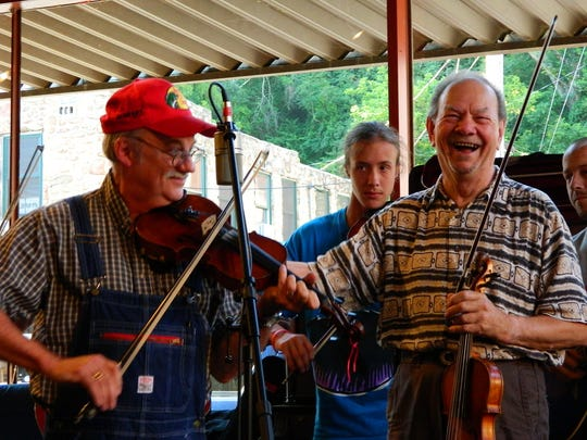 Local fiddlers Roger Howell (left) and Bobby Hicks share a smile during a Thursday night jam inside Zuma Coffee.