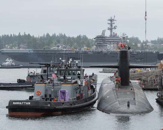 The USS Nimitz aircraft carrier passes before the USS Maine ballistic missile submarine. The Maine recently completed a 30-month, $371 million overhaul at the Puget Sound Naval Shipyard.