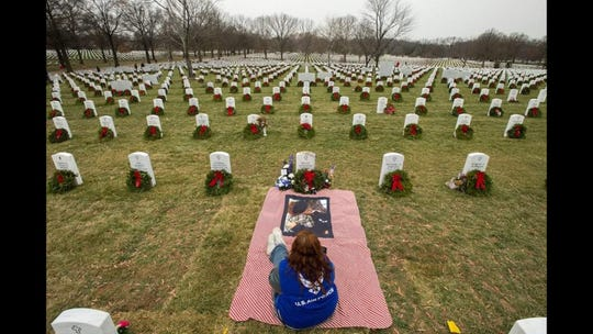 Cathy Powers sits at son Bryce's grave at Arlington National Cemetery.