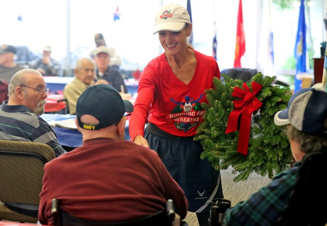Cathy Powers shakes hands with Washington State Veterans Home resident Stanley Hansen after her presentation of a wreath to the home on Friday. Powers is logging running miles in every state, visiting veterans and raising money for Wreaths Across America.