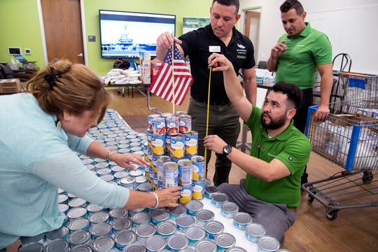 Olivia Fischer (clockwise from left), Robert Ponce, Eriel Soto and Miguel Lujan create a replica of the USS Lexington Museum on the Bay out of canned goods on Friday, June 14, 2019 at the Humana Neighborhood Center. Humana, the Veterans of Foreign Wars and the Coastal Bend Food Bank partnered to create the replica with canned food to bring awareness to food insecurity in veterans and military families. The donated food was set to go to the food bank when they were finished.