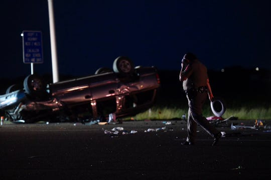 State Troopers and Texas Wrecker crew members clean debris from the crash.