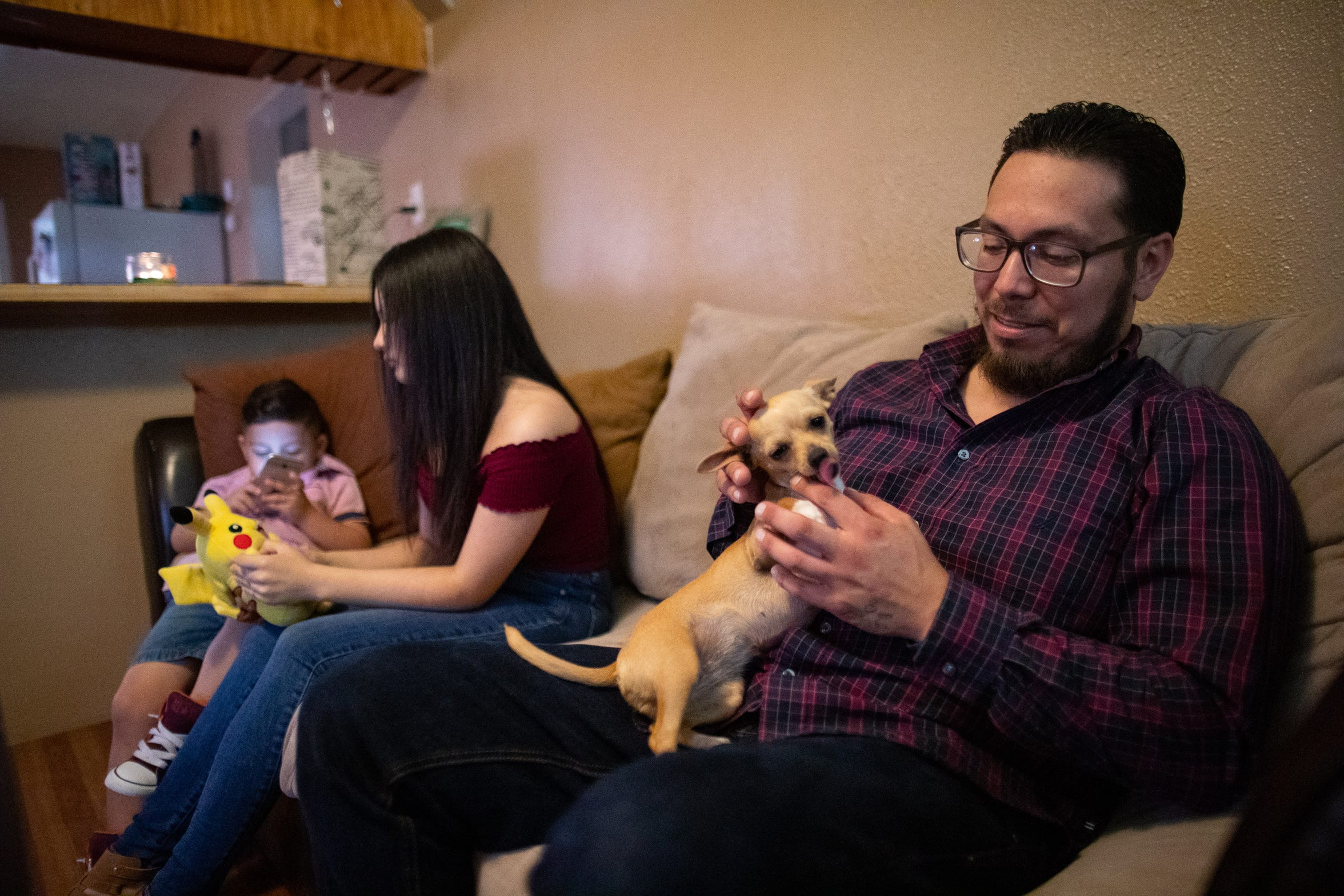 Jose Zavala, a disabled Army veteran, pets his dog as he sits down with his wife, Monica, and five kids at their home in Robstown, on Friday, June 14, 2019.