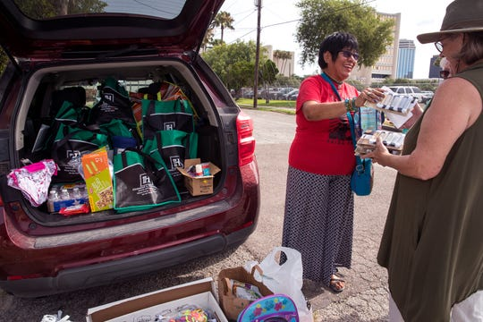 Dora Wilburn (left) delivers shoelaces to Julie Rogers at the RAICES office on Friday, June 14, 2019. A group of Corpus Christi women dismayed by the separation of migrant families began a shoelace drive a couple of weeks before Mother's Day. The collection will last until this weekend and will then be delivered to Brownsville to help migrants.