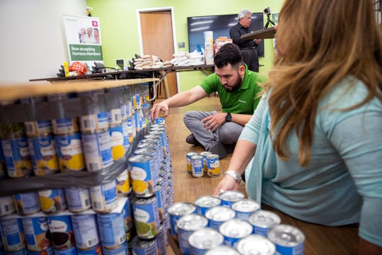 Olivia Fischer (front) and Miguel Lujan create a replica of the USS Lexington Museum on the Bay out of canned goods on Friday, June 14, 2019 at the Humana Neighborhood Center. Humana, the Veterans of Foreign Wars and the Coastal Bend Food Bank partnered to create the replica with canned food to bring awareness to food insecurity in veterans and military families. The donated food was set to go to the food bank when they were finished.