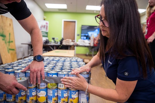 Elizabeth Cantu helps create a replica of the USS Lexington Museum on the Bay out of canned goods on Friday, June 14, 2019 at the Humana Neighborhood Center. Humana, the Veterans of Foreign Wars and the Coastal Bend Food Bank partnered to create the replica with canned food to bring awareness to food insecurity in veterans and military families. The donated food was set to go to the food bank when they were finished.