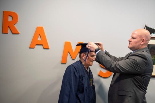 Pricipal Adam Lee adjusts the cap of Vietnam veteran George Schaefer, 67, Friday, June 14, 2019 at Overbrook High School in Pine Hill, N.J. Schaefer will receive his diploma 50 years after leaving school to enlist in the military.