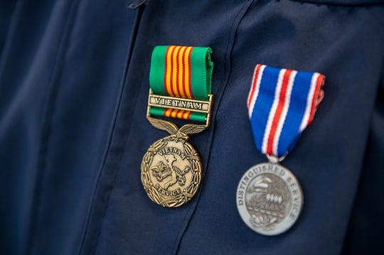 Vietnam veteran George Schaefer's service awards pinned to his graduation gown.