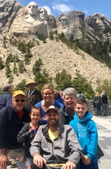 Paul and Leslie Rinderknecht of Springfield Township, center, are on a family RV vacation to see national parks out West. Paul is living with the progressive paralysis known as Lou Gehrig's disease. On Wednesday, the family  got to Mount Rushmore. From left, Doug Spears, Leslie's father' the couple's daughter Nora; Leslie; Paul, Ann Spears, Leslie's mother, and the couple's son Leo.