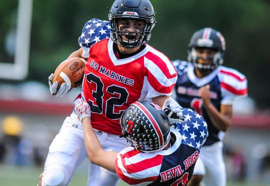 Joseph Ciempola of Somerville breaks a tackle by PJ Chisholm of Bernards in the Basilone Bowl in Bridgewater on June 13, 2019.