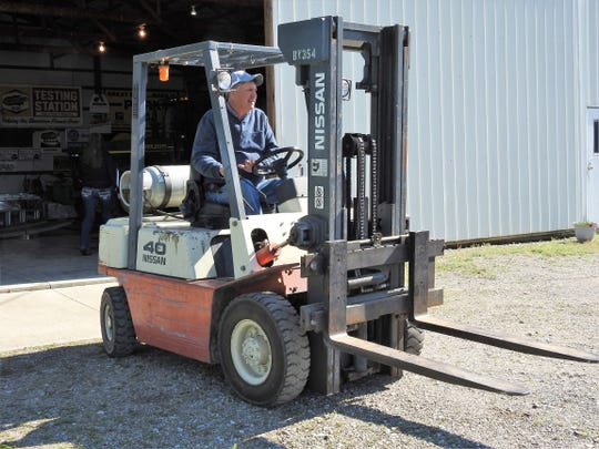 Steven Finton drives a fork lift out of the barn to help carry in parts for a new grain bin. He's projecting a good year and that's why a new bin is being put up.