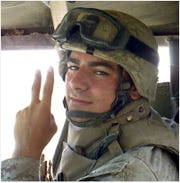 Norwalk Superhero Clay Garcia flashes the peace sign while on a vehicle mounted patrol in Fallujah, Iraq.