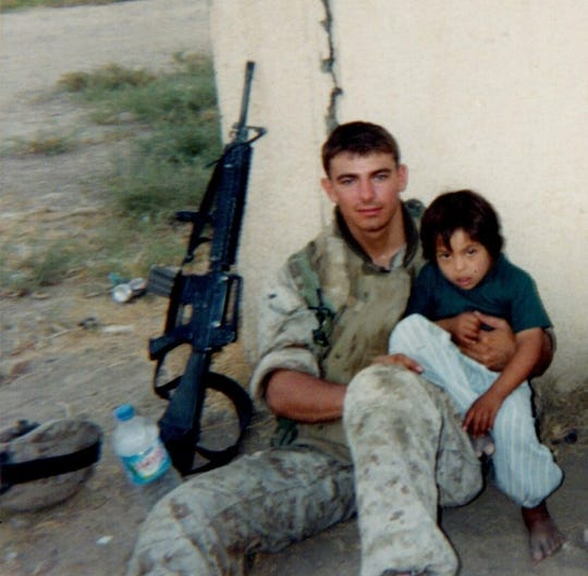 """Norwalk """"superhero"""" awardee Clay Garcia served two tours in Iraq. This photo, taken outside the unit's operating base right before heavy fighting in Fallujah that resulted in him receiving a Bronze Star, includes a local child who befriended the troops and accompanied them on many patrols."""