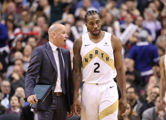 Toronto Raptors assistant coach Nate Bjorkgren talks to forward Kawhi Leonard (2) during a game against the Portland Trail Blazers at Scotiabank Arena in Toronto on March 1, 2019.