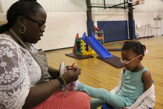 Cindy Lester ties a shoelace during gym class at Children of the Rising Sun Empowerment Center in northwest Detroit.