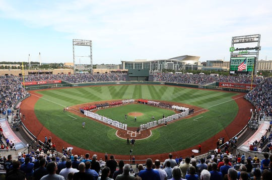 A general view as the players from each of the 8 College World Series teams line up with the Detroit Tigers and the Kansas City Royals during the National Anthem ahead of the game at TD America Park on June 13, 2019 in Omaha, Nebraska.