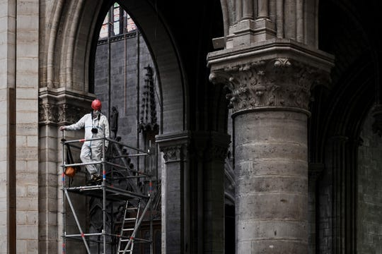 A worker stands on scaffolding during preliminary work inside the Notre Dame de Paris Cathedral, in Paris.  The billionaire French donors that publicly promised flashy donations totalling hundreds of millions to restore Notre Dame, have not yet paid a penny toward the restoration of the French national monument, according to church and business officials.