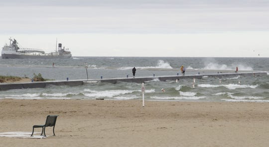 People walk on the north breakwater at Stearns Park Beach on Monday as the Mississagi comes into port before police closed it due to waves crashing over the wall.