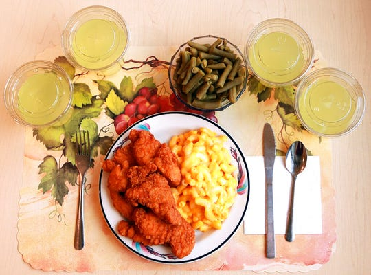 "This undated photo provided by the National Institutes of Health in June 2019 shows an ""ultra-processed"" lunch including brand name macaroni and cheese, chicken tenders, canned green beans and diet lemonade. Researchers found people ate an average of 500 extra calories a day when fed mostly processed foods, compared with when the same people were fed minimally processed foods. That's even though researchers tried to match the meals for nutrients like fat, fiber and sugar."