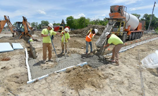 Novi Wall Foundations and Footings employees dig trenches and pour concrete into the building's foundations  Friday afternoon.
