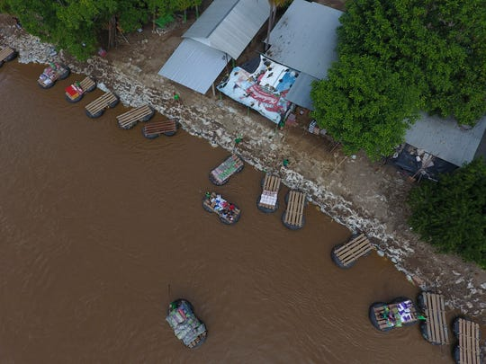 Inner tube and plank rafts ferry passengers and merchandise freely across the Suchiate River between Ciudad Hidalgo, Mexico, and Guatemala (not pictured), Thursday, June 13, 2019.
