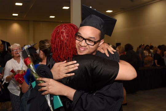 Emmanuel Franklin gets a well-deserved hug from his mother Enomwoyi Franklin after receiving his high school diploma from the Michigan Virtual Charter Academy.