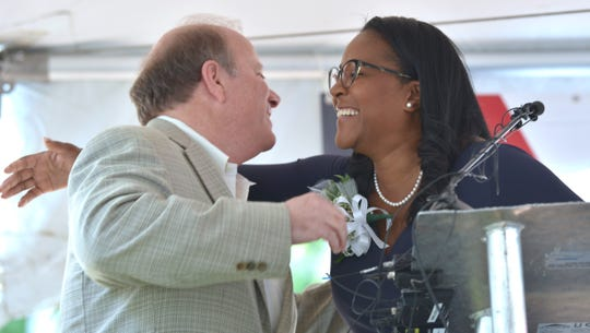 Detroit Mayor Mike Duggan hugs Linda Little, president & CEO of the Neighborhood Service Organization, as she introduces the mayor at the podium before presenting him with 'A Man in the City for a Man of the City' award.