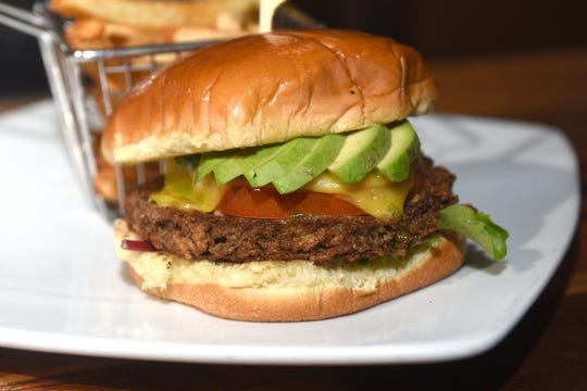 The Impossible Burger with veganaise, tomato, vegan mozzarella, lettuce, arugula pesto, and avocado is seen at Ale Mary's in downtown Royal Oak on February 22, 2018. Large restaurant chains Red Robin and White Castle are reporting shortages of Impossible Foods Inc.'s popular meat-free patties on June 14, 2019.