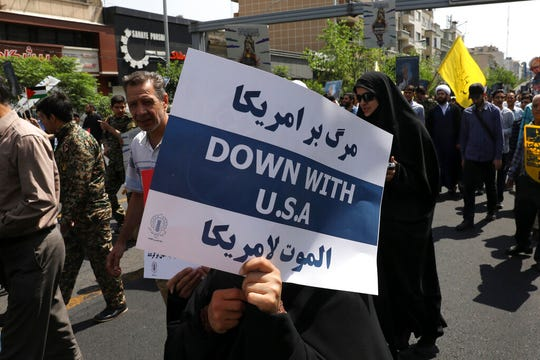 In this May 31, 2019 file photo, a demonstrator holds an anti-U.S. placard during the annual Quds, or Jerusalem Day rally in Tehran, Iran. The top line on the placard in Farsi translates to, Death to America, and the bottom line on the placard in Arabic translates to, Death to America.