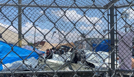 In this June 1, 2019, photo, provided by New Mexico State University professor Neal Rosendorf, migrants are seen through fencing inside a temporary outdoor encampment where they're waiting to be processed in El Paso, Texas.