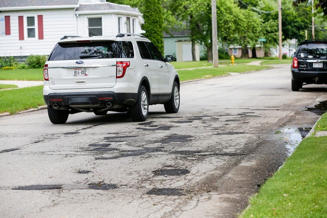A vehicle passes by an area where multiple potholes have been filled Friday, June 14, 2019 on Grove Street in Fond du Lac, Wis. Doug Raflik/USA TODAY NETWORK-Wisconsin