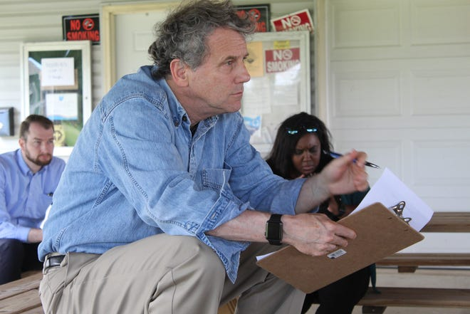 U.S. Senator Sherrod Brown takes notes during a discussion with elected officials, scientists and business people that work along Lake Erie in Ottawa County last year.