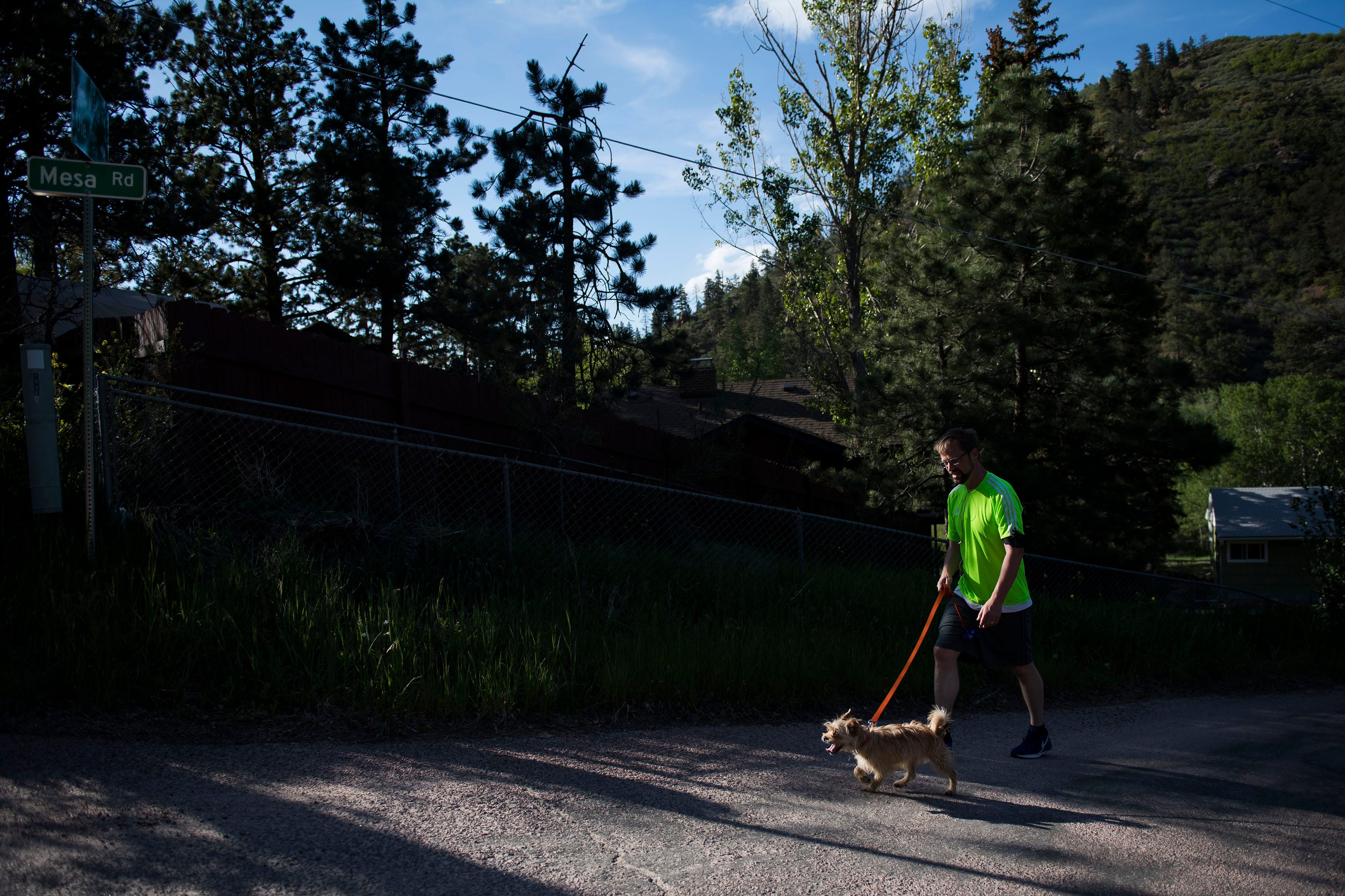 Nine-year resident Jamie Berry takes his dog Goldie for a walk up the steep hills in his neighborhood on Wednesday, June 12, 2019, in Cascade, Colo.