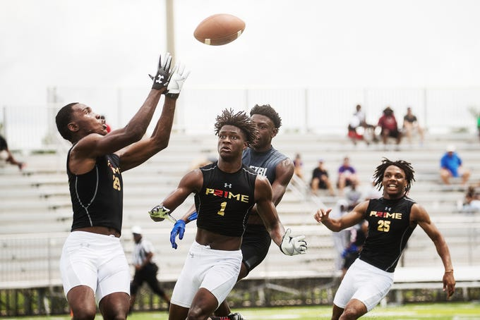 From left, Charles Toombs, Omarion Cooper and Jason Joseph from the Lee County All Stars  go up  for an interception in front of a pass intended for the Mississippi Grind's Emmanuel Forbes during a scrimmage game at Bishop Verot High School. Deion Sanders is expanding his 7v7 league to Southwest Florida. Forbes is committed to Mississippi State