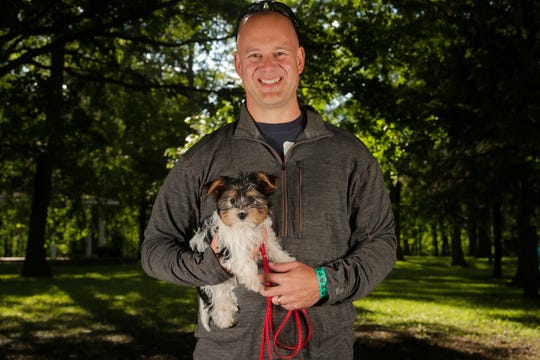 Joel Johnson of De Pere and his dog Kona at the Pooches & Pints popup dog park at Green Isle Park on Thursday, June 13, 2019 in Allouez, Wis.