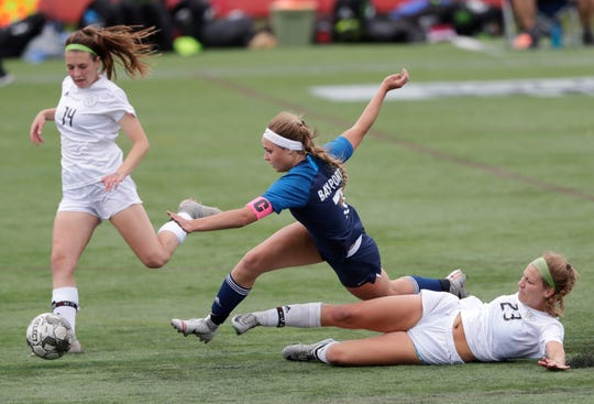 Bay Port's Mac Johnson (23) is brought down by Divine Savior Holy Angels' Sydney Schaaf (23) as Emilie Harwood (14) tries to get control of the ball during a WIAA Division 1 girls state soccer semifinal Friday at Uihlein Soccer Park in Milwaukee.