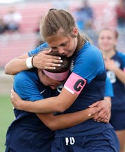 Bay Port's Grace Krause and Madi Noe (10) embrace after losing 1-0 against Divine Savior Holy Angels in a WIAA Division 1 girls state soccer semifinal Friday at Uihlein Soccer Park in Milwaukee.