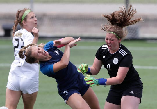Bay Port's Mac Johnson collides headfirst with Divine Savior Holy Angels goalie Jillian VanTreeck (0) during a WIAA Division 1 girls state soccer semifinal Friday at Uihlein Soccer Park in Milwaukee. Both players had to be helped off the field.