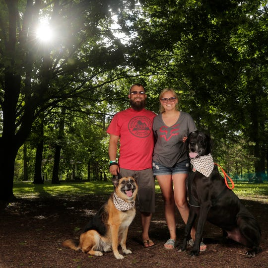 Jesse Schroeder, Oshkosh, and Elizabeth Moore of Allouez with their dogs Charlie, left and Rocky at the Pooches & Pints popup dog park at Green Isle Park on Thursday, June 13, 2019 in Allouez, Wis.